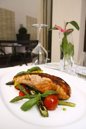 The dish of grilled salmon and some vegetables photo