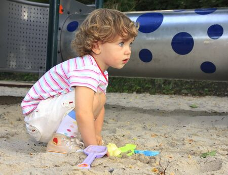 The little child playing in the sandbox photo