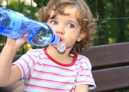 The little girl is drinking water from the plastic bottle. Stock Photo