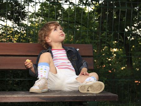 curled lip: The child is looking up to the sky, sitting on the bench.
