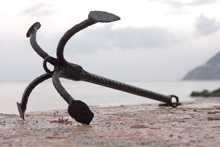 ship anchor: The old rusty anchor lying on the pier.