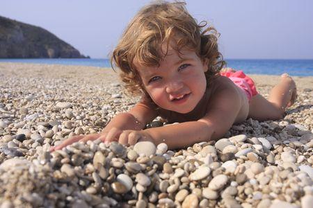 sunbath: De lachende kind is het nemen van een bad van de zon op het strand.