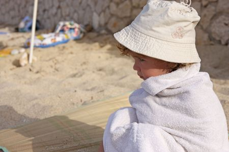 muffle: The child wrapped in a towel is sitting on the beach.