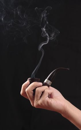 Hand of man with a smoking tobacco-pipe. photo