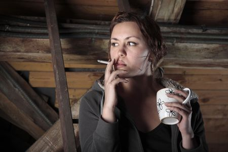 Young woman is drinking coffee and smoking cigarette on the garret. Stock Photo
