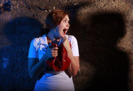 squeal: Giovane donna squittendo con orrore al muro arrugginito. Lei � spaventata da qualcuno pericoloso. Archivio Fotografico