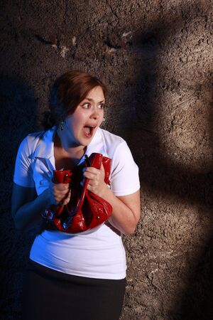 squealing: Young woman squealing with horror at the rusty wall. She is scared by someone dangerous. Stock Photo