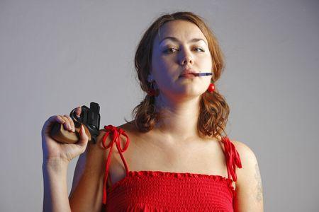 Girl in red is playing with a black revolver and smoking a cigarette photo