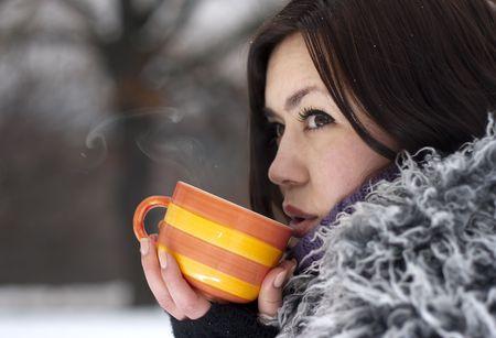 ropa de invierno: Mujer joven con una bebida caliente en invierno al aire libre.  Foto de archivo