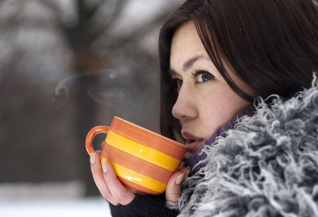 Young woman having a hot drink in winter open air. Фото со стока