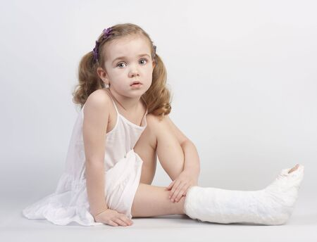 plaster foot: Little girl injured with broken ankle sitting on white backgound. Stock Photo