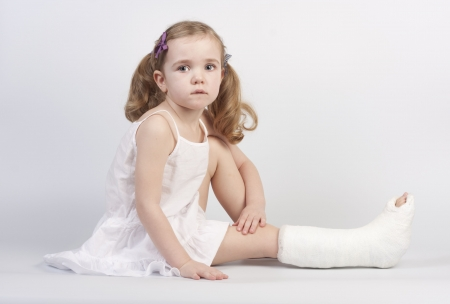 Little girl injured with broken ankle sitting on white backgound. Stock Photo