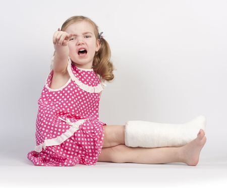 broken foot: Little girl injured with broken ankle sitting on white backgound. Stock Photo