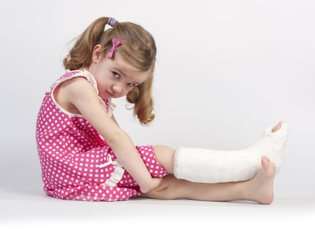 Little girl injured with broken ankle sitting on white backgound. Фото со стока