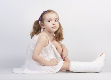 bandage: Little girl injured with broken ankle sitting on white backgound.  Stock Photo