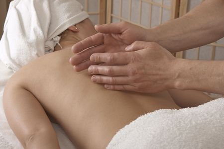 Woman is getting back massage from a physiotherapist. photo