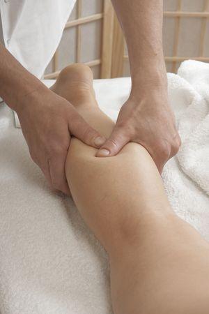 masoterapia: Manos de Masajeador trabajando con la pierna de una mujer. Práctica de reflexoterapia.