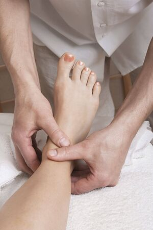 Massagers hands working with a womans foot. Practice of reflexotherapy.