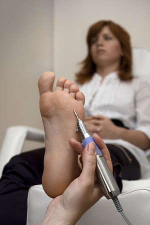 Young woman is taking the foot peeling procedure   photo