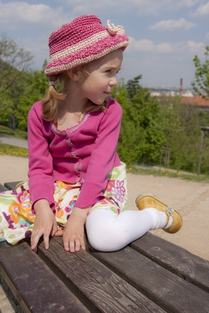 Little girl dressed in pink is sitting outdoor.