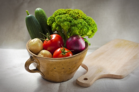 Still life with the clay pot full of vegetables and the breadboard on the tablecloth.  photo