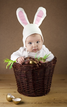 bunny ears: Little baby dressed as a bunny sitting in a wicker basket, which is full of golden eggs  Good as an Easter greetings