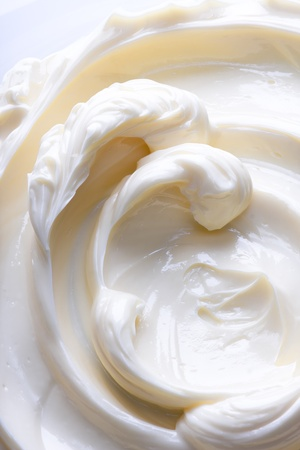 lowfat: Swirling surface of light beige low-fat milky cream. Close-up photo.