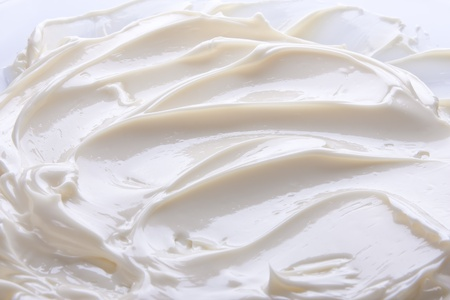 Wavy surface of light beige low-fat milky cream. Close-up photo. photo