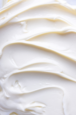 lowfat: Wavy surface of light beige low-fat milky cream. Close-up photo. Stock Photo