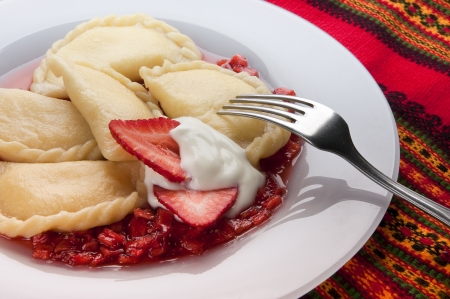 pierogi: Varenyky or pierogy stuffed with cottage cheese, served with sour cream and strawberry sauce  A traditional Ukrainian or Polish dessert