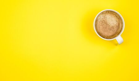 Top view image of coffe cup on wooden yellow background. Flat lay. Copy space