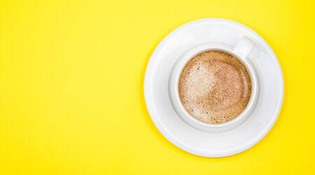 Immagine vista dall'alto della tazza di caffè su sfondo giallo in legno. Disposizione piatta. Copia spazio Archivio Fotografico