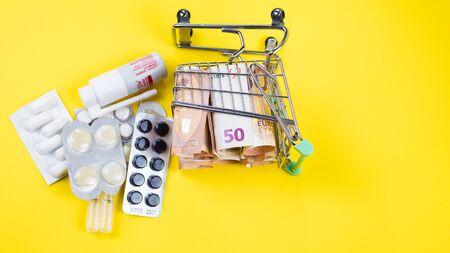 shopping cart fshopping cart full of medicine with pills and capsules and euro banknotes. money . drug cost conceptull of medicine with pills and capsules and euro banknotes. money . drug cost concept