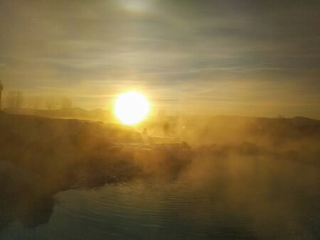 Hot spring, blurred photo of morning fog over pool in cold autumn weather at Terme Italy.