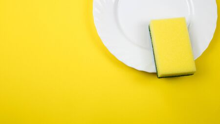 Cleaning sponge on a white plate on a yellow background.