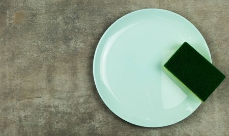 Cleaning sponge on a green plate on a gray background.