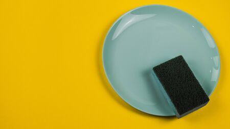 Cleaning sponge on a green plate on an orange background.