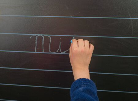 Little schoolboy writing on blackboard at home.