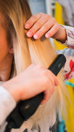 blond woman in the bathroom straightens her hair with a curling iron. Banque d'images
