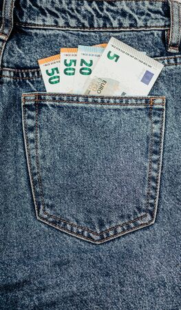 fifty euro bills in the back pocket of denim pants. concept.