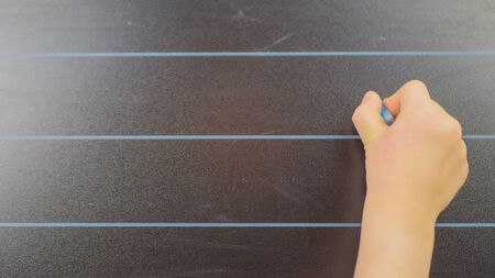 schoolboy hand writes in chalk on a blackboard during a lesson at schoo. Banque d'images