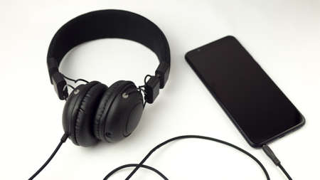 black phone with headphones on a white background.