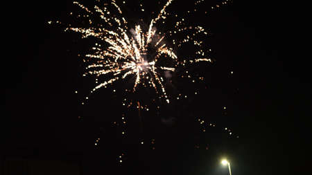 Orange blurred firework lights on black sky background. Concept of New Year and Christmas.