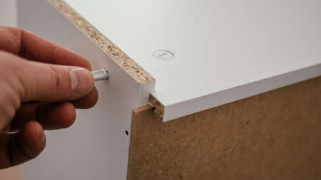 the process of assembling furniture from chipboard with a cordless screwdriver, close-up