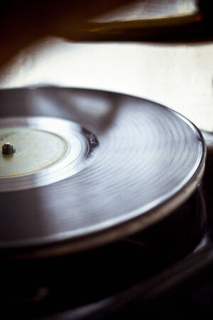 A old vinyl record album plays on a turntable.