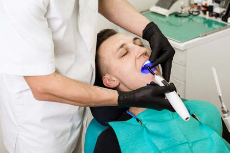 Dentist shine a bright blue Light in the male patients mouth to harden composite filling. Dental treatment process