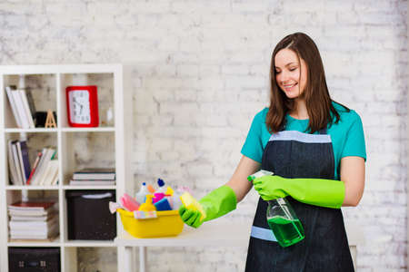 Young woman janitor spraying detergent on the sponge, standing in a modern house. Professional cleaning of apartments