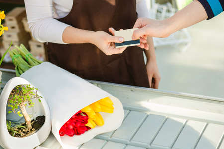 buyers hand giving payment card for payment flowers to saleswoman. Cashless payments Stock Photo