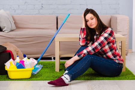 Moe jonge vrouw op de grond zitten, thuis, na het schoonmaken van het huis. Naast haar is een mop en een emmer met schoonmaakmiddel.