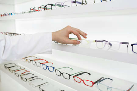 oculist selects a frame for glasses to correction of vision, at the white showcase with many glasses